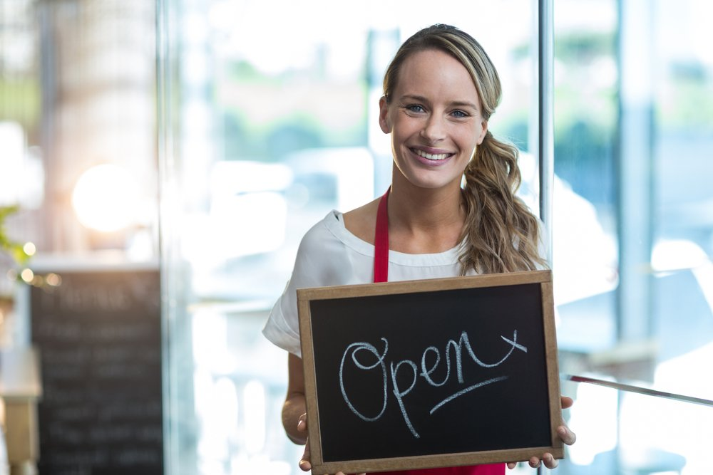 Portrait of smiling waitress showing slate with open sign in cafe